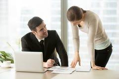 Businessman and businesswoman negotiating over building plan, di Stock Photos