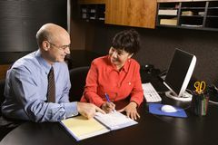 Businessman and businesswoman in office. Royalty Free Stock Images