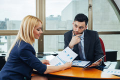 Businessman and businesswoman in office looking at business document Stock Images
