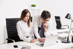Businessman and businesswoman in office. Businesswoman sitting at office table and making notes. Businessman next to her showing something on her laptop. Concept stock photo