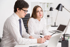 Businessman and businesswoman in office. Young businessman looking at laptop screen and making notes, businesswoman next to him looking aside. Concept of royalty free stock images
