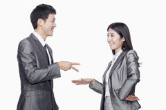 Businessman and businesswoman in playful gesture, studio shot Stock Image
