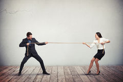 Businessman and businesswoman playing tug of war Royalty Free Stock Image