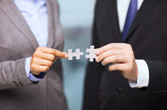 Businessman and businesswoman with puzzle pieces Stock Images