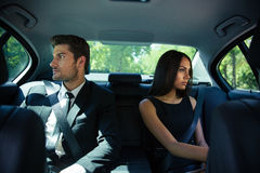 Businessman and businesswoman riding in car Royalty Free Stock Photo