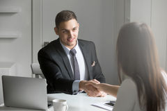 Businessman and businesswoman shaking hands in agreement Royalty Free Stock Image