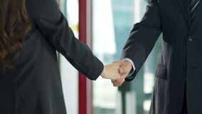 Businessman and businesswoman shaking hands. Business man and woman meeting at elevator area and shaking hands stock video footage
