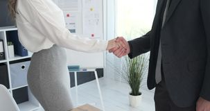 Businessman and businesswoman shaking hands. In office stock footage