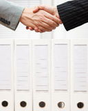 Businessman and businesswoman are shaking hands over company doc Royalty Free Stock Photography