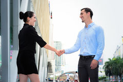 Businessman and businesswoman shaking hands and smile for success business agreement. At the outdoor place Stock Photo