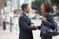 Businessman And Businesswoman Shaking Hands In Street Stock Photos