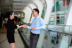 Businessman and businesswoman shaking hands for success agreement and talk about business Stock Images