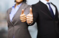 Businessman and businesswoman showing thumbs up royalty free stock photography