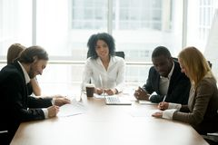 Businessman and businesswoman signing contracts at group multira. Cial meeting, two smiling male and female new partners making deal after successful royalty free stock photo