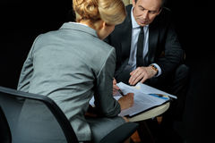 Businessman and businesswoman signing papers together stock photo