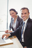 Businessman and businesswoman sitting in conference room Royalty Free Stock Image