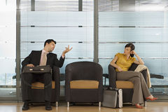 Businessman and businesswoman sitting in office reception area, talking, man gesturing Royalty Free Stock Photography