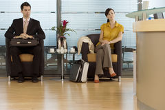 Businessman and businesswoman sitting in office reception area, waiting patiently royalty free stock photography