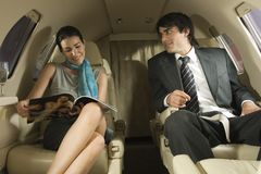 Businessman and businesswoman sitting in a private airplane Stock Images
