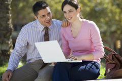 Businessman and businesswoman sitting on wall, woman using laptop in lap, smiling Stock Photo