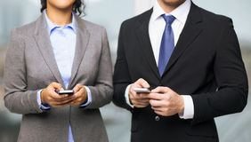 Businessman and businesswoman with smartphones Stock Images