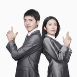 Businessman and businesswoman standing back to back and showing hand guns, studio shot Stock Photo