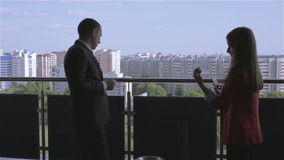 Businessman and businesswoman are standing on a balcony. Man in suit is smoking a cigarette, woman in a red jacket with mobile phone in hands. Slow motion stock video