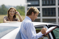 Businessman and businesswoman standing beside car, smiling, woman using mobile phone, man writing Stock Photos