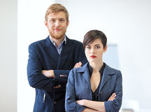 Businessman and businesswoman standing with crossed arms. Team w Stock Photography