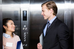 Businessman and businesswoman standing in an elevator. In office royalty free stock photography
