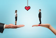 Businessman and businesswoman standing on the hands with drawn heart between them. Stock Image