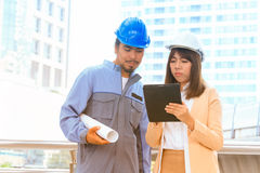 Businessman and businesswoman standing using digital tablet Stock Photo