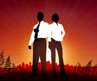 Businessman and Businesswoman on sunset background Stock Image