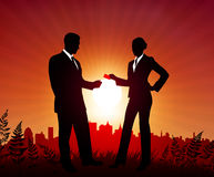 Businessman and Businesswoman on sunset background Royalty Free Stock Photography