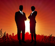 Businessman and Businesswoman on sunset background Stock Photos