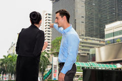 Businessman and businesswoman talk about business outdoor. He Point the finger at somewhere Stock Photo