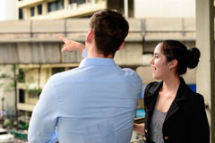 Businessman and businesswoman talk about business outdoor, he Point the finger to building Stock Photo