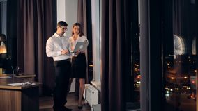 Business partners stand near a window and discuss work on a laptop. A businessman and a businesswoman talk and look at one laptop near a tall office window stock video footage