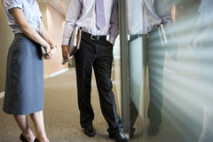 Businessman and businesswoman talking in corridor beside office window, low section, side view Stock Image