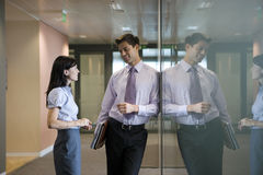 Businessman and businesswoman talking in office corridor, smiling, side view, reflection in glass Stock Photography