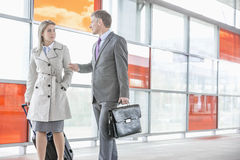 Businessman and businesswoman talking while walking on railroad platform Stock Photos