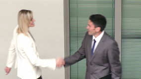 Businessman and businesswoman talking about work in corridor. Businessman and businesswoman shaking hands and talking about work in corridor footage in High stock footage