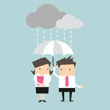 Businessman & businesswoman under umbrella in the rain Stock Image