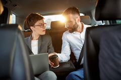 Businessman and businesswoman using laptop in back seat of car Royalty Free Stock Images