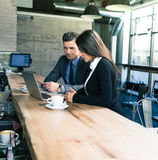 Businessman and businesswoman using laptop in cafe Stock Images