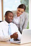 Businessman And Businesswoman Using Laptop In Office Royalty Free Stock Photography
