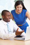 Businessman And Businesswoman Using Laptop In Office Royalty Free Stock Images