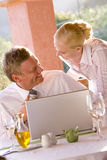 Businessman and businesswoman using laptop on restaurant balcony Stock Photography