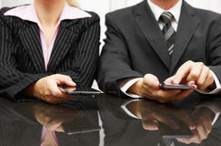 Businessman and businesswoman using smart phone on meeting Royalty Free Stock Photography
