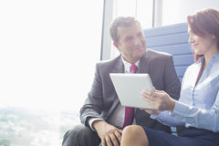 Businessman and businesswoman using tablet PC in office Royalty Free Stock Images